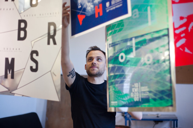 Back to reality: Krzysztof Iwanski reaching for hanging posters