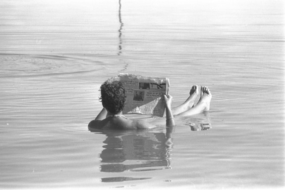 A man reading a newspaper while bathing in the Dead Sea