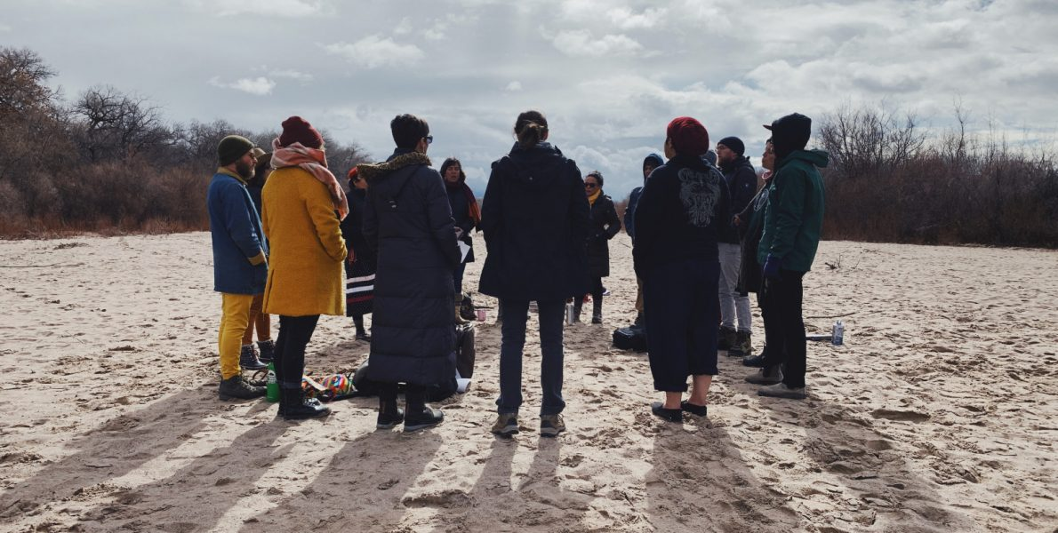 A circle of people dressed for cold weather standing in a circle on sand - Pyragraph